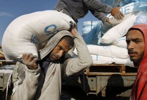 A Palestinian carries a sack of flour received from the United Nations Relief and Works Agency (UNRWA) headquarters in Khan Younis in the southern Gaza Strip January 19, 2009. Israeli forces were pulling out of the Gaza Strip on Monday following a tentative truce with Hamas that allowed Palestinians to take stock of the devastating three-week war.  REUTERS/Ibraheem Abu Mustafa (GAZA)