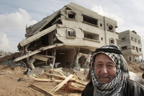 A Palestinian man passes a house destroyed during Israel's offensive in Jabalya in the northern Gaza Strip January 19, 2009. Palestinians took stock on Monday of the devastation from a three-week war in the Gaza Strip as a ceasefire took hold and Israeli forces pressed on with their gradual withdrawal from the Hamas-ruled territory. REUTERS/Mohammed Salem (GAZA)