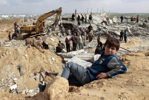 A Palestinian boy sits near houses destroyed during Israel's offensive in Jabalya in the northern Gaza Strip January 19, 2009. Palestinians took stock on Monday of the devastation from a three-week war in the Gaza Strip as a ceasefire took hold and Israeli forces pressed on with their gradual withdrawal from the Hamas-ruled territory.  REUTERS/Mohammed Salem (GAZA)