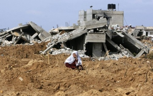 A Palestinian woman sits in front of houses destroyed during Israel's offensive in Jabalya in the northern Gaza Strip January 19, 2009. Palestinians took stock on Monday of the devastation from a three-week war in the Gaza Strip as a ceasefire took hold and Israeli forces pressed on with their gradual withdrawal from the Hamas-ruled territory.  REUTERS/Mohammed Salem (GAZA)