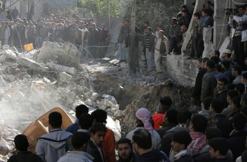 Palestinian gather next to the debris of a three-storey house belonging to a Hamas member that was destroyed by an Israeli bomb in the eastern Gaza City neighborhood of Zeitun on January 6, 2009. Israeli troops battled Hamas fighters in major cities of overcrowded Gaza today as Israel spurned appeals to halt a war on the Islamists that has killed at least 580 Palestinians. Israeli tanks firing cannons and backed by helicopter gunships rolled into the southern city of Khan Yunis in the pre-dawn hours, to be met by return fire from Hamas and other militant groups, witnesses said. AFP PHOTO/MAHMUD HAMS (Photo credit should read MAHMUD HAMS/AFP/Getty Images)
