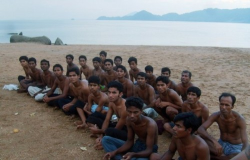Rohingya migrants sit on a beach on Koh Sai Daeng in southwest Thailand while being processed by Thai authorities in this undated photo obtained by CNN. Pressure mounted on Thailand on January 26, 2009 to come clean on allegations the army towed Rohingya refugees out to sea and abandoned them in engine-less boats, after CNN showed pictures depicting exactly that.