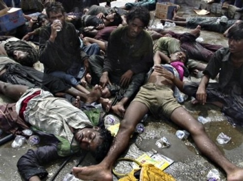Ethnic Rohingya refugees lay sprawled on the ground after being rescued by Acehnese fishermen Jan. 7, 2009 on Sabang, an island off the coast of Banda Aceh, Indonesia.  One hundred ninety-three men of Rohingya ethnicity, 17 from Bangladesh and the others from Myanmar, allege that they were mistreated by Thai soldiers and then towed to sea and left to drift with inadequate supplies. (AP Photo/Taufik Kurahman)
