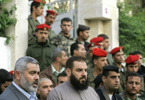 (FILES) Surrounded by Palestinian security, Hamas senior leader Ismail Haniya (L) speaks to the press as Nizar Rayan (C) listens on during a press conference outside the Palestinian Elections Committee headquarters in Gaza City, 14 December 2005. Senior Hamas leader Nizar Rayan was killed in an Israeli air strike on January 1, 2009.  AFP PHOTO/MAHMUD HAMS (Photo credit should read MAHMUD HAMS/AFP/Getty Images)