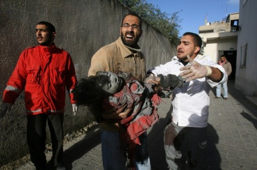 Palestinians carry the body of a little girl following an Israeli air strike targeting the house of Senior Hamas leader Nizar Rayan in Gaza City on January 1, 2009. Rayan was killed today with his four wives and two of his children in an Israeli air strike in Gaza, medics said. AFP PHOTO/MOHAMMED ABED (Photo credit should read MOHAMMED ABED/AFP/Getty Images)