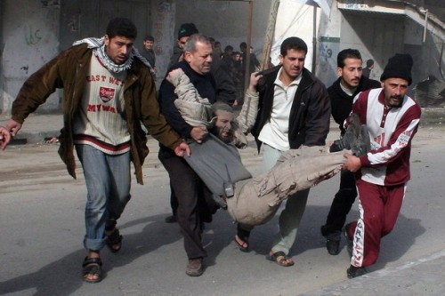 A Palestinian carries a wounded man following an Israeli air strike in Gaza city on January 1, 2009. Israel killed a top Hamas commander today in the biggest blow yet against the Islamist leadership as dozens more air strikes on Gaza took the death toll from the six-day blitz above 400. AFP PHOTO/MOHAMMED AL-ZAANOUN (Photo credit should read MOHAMMED AL-ZAANOUN/AFP/Getty Images)