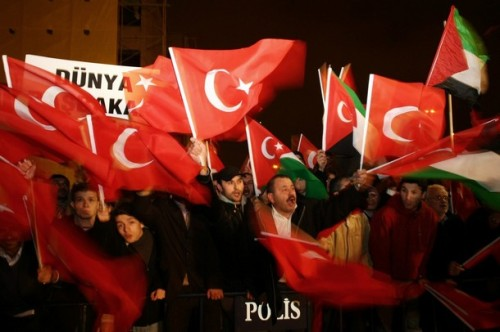 Supporters of Justice and Developpment Party (AKP) wave national and Palestinian flags as Turkish Prime Minister Recep Tayyip Erdogan arrives at Ataturk International Airport in Istanbul, early January 30, 2009. Erdogan stormed out of a debate with Israeli President Shimon Peres about the Gaza war at the Davos forum. AFP PHOTO / MUSTAFA OZER (Photo credit should read MUSTAFA OZER/AFP/Getty Images)