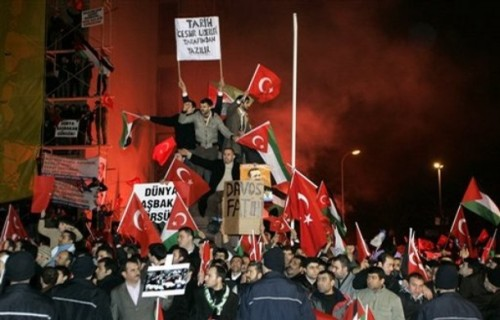 Supporters of the ruling Justice and Development Party, or AKP, wave Turkish and Palestinian flags outside the Ataturk International Airport in Istanbul, Turkey, early Friday, Jan. 30, 2009, as they wait for the arrival of the Turkish Prime Minister Recep Tayyip Erdogan, who they see as a hero for stalking out of a panel at the World Economic Forum in Davos, Switzerland, after indicting Israeli President Shimon Peres for Israel's offensive on Gaza. (AP Photo/Ibrahim Usta)