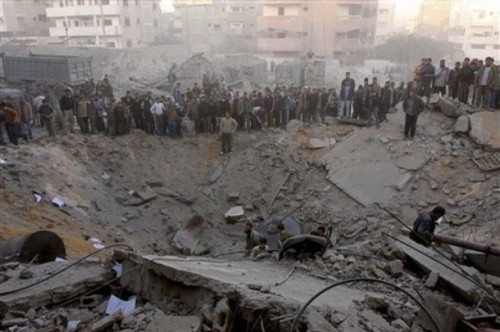 Palestinians gather around the crater caused by an Israeli strike which hit the house of top Hamas official Said Siam's brother in Gaza City, Thursday, Jan. 15, 2009. Officials from the Israeli military and Shin Bet security agency said Siam was killed while hiding in his brother's home in Gaza City. Siam is considered to be among Hamas' top five leaders in Gaza.  Palestinian medical officials confirmed the house was attacked, but there was no word from Hamas on Siam's fate. (AP Photo/Khalil Hamra)