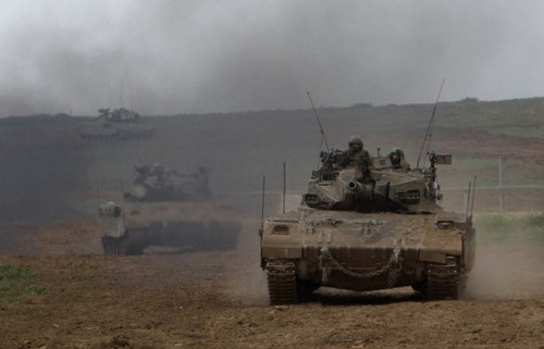 Israeli tanks roll across the border into Israel from the Gaza Strip January 19, 2009. Israeli forces were pulling out of the Gaza Strip on Monday following a tentative truce with Hamas that allowed Palestinians to take stock of the devastating three-week war.  REUTERS/Ronen Zvulun