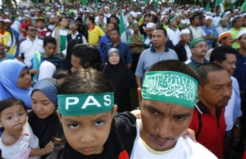 An opposition supporters and his daughter wear Pan-Malaysian Islamic Party (PAS) head bands during a nomination in Taiping, Northern state of Perak ,300 kilometers (187 miles) from Kuala Lumpur, Sunday, March 29 2009. Malaysian politicians launched their campaign Sunday for three legislative seats in special elections seen as a crucial test for the ruling party's new leaders. (AP Photo