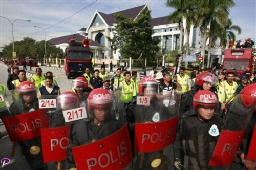 Riot police stand guard in front of state government office, background, where an assembly is supposed to be held in Ipoh, Perak state, Malaysia, Tuesday, March 3, 2009. Riot police and ruling party supporters blocked members of an opposition coalition from entering a northern state's parliament Tuesday in an increasingly tense tussle for its control. The spat in Perak state highlights the growing instability in Malaysian politics since the March 2008 elections when the National Front coalition that controls the national government suffered its worst results ever. (AP Photo/Vincent Thian)