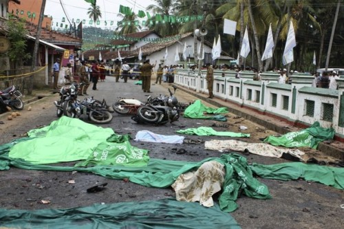The covered bodies of those killed by a bomb blast are seen outside a mosque in Godapitiya in Matara district, about 160 km (99 miles) south of the capital Colombo, March 10, 2009. A suspected Tamil Tiger suicide bomber killed 14 people and wounded 35, including Sri Lanka's telecommunications minister, during a Muslim festival in the island's south on Tuesday, officials said.    REUTERS/Stringer (SRI LANKA CONFLICT POLITICS IMAGE OF THE DAY TOP PICTURE)
