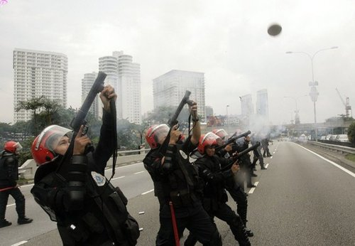 Malaysian riot police fire tear gas at demonstrators protesting against the use of the English language in teaching science and mathematics at schools, in Kuala Lumpur March 7, 2009. Malaysian police fired tear gas to disperse hundreds of opposition activists demanding that science and math be taught in the national Malay language, witnesses said.  Language is a sensitive issue for the country's majority Malays and represents the latest political battleground for incoming Prime Minister Najib Razak, who is already facing a challenge from a weakening economy.   REUTERS Pictures