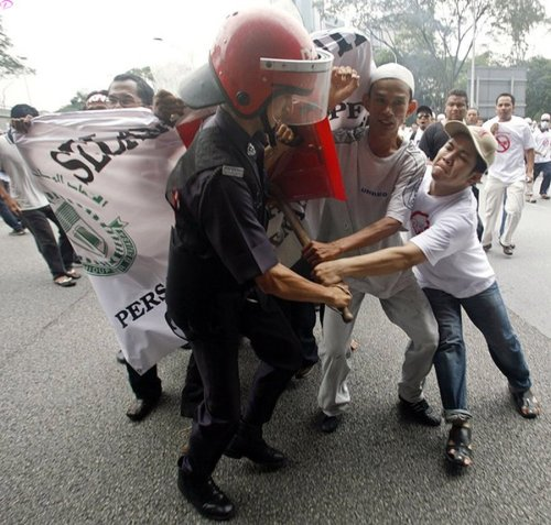 A riot policeman scuffles with demonstrators during a protest against the use of the English language in teaching science and mathematics at schools, in Kuala Lumpur March 7, 2009. Malaysian police fired tear gas to disperse hundreds of opposition activists demanding that science and math be taught in the national Malay language, witnesses said. Language is a sensitive issue for the country's majority Malays and represents the latest political battleground for incoming Prime Minister Najib Razak, who is already facing a challenge from a weakening economy.         REUTERS PICTURES