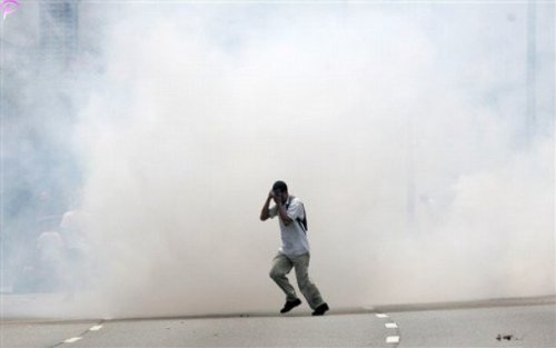 A protester covers himself as he runs away from tear gas fired by Malaysian riot police during a protest against using English for mathematics and science teaching in Kuala Lumpur, Malaysia, Saturday, March 7, 2009.AP Photo