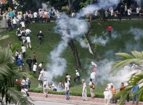 Protesters run away from tear gas fired by Malaysian riot police during a protest against the use of English to teach math and science  in Kuala Lumpur, Malaysia, Saturday, March 7, 2009.
