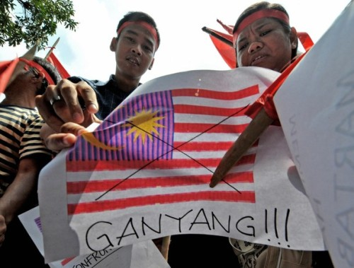 """Indonesians hold up pictures of the Malaysian flag as well as other placards, saying """"ganyang"""" or attack, during an anti-Malaysia protest in Jakarta on August 30, 2009 after the neighbouring country was accused of using Indonesian traditional dances to promote Malaysian tourism.  Indonesian President Susilo Bambang Yudhoyono has asked the Malaysian government to deal more carefully with """"sensitive"""" cultural issues between the two countries, after a recent Malaysian tourism advertisement, a 30-second video clip, showed Balinese """"Pendet"""" dancing.   AFP PHOTO / Bay ISMOYO (Photo credit should read BAY ISMOYO/AFP/Getty Images)"""