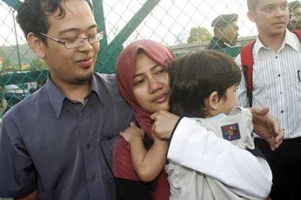 TAHANAN ISA DIBEBASKAN... Naim Jusri memeluk isterinya Nussaibah Ariffin dan anaknya Masirah naim sebaik dibebaskan oleh polis kerana menyertai demonstrasi anti-ISA kelmarin.--foto THE STAR