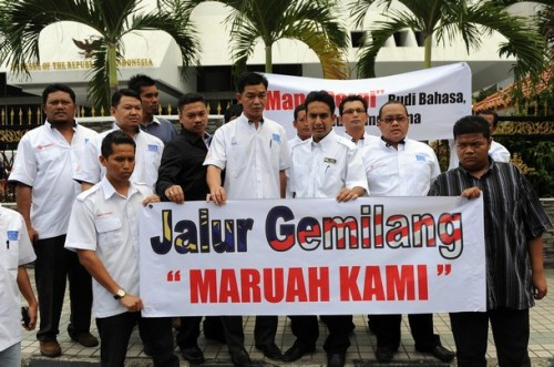 Members of Malaysian ruling party United Malays National Organisation (UMNO) youth wing march with banners in front of the Indonesian embassy in Kuala Lumpur