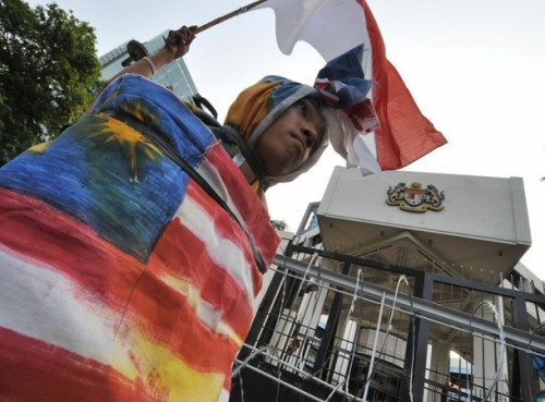 "A protester covers his body with a Malaysian flag during a rally in front of the Malaysian embassy in Jakarta on September 10, 2009. Malaysia said it had summoned Indonesia's ambassador to express ""grave concern"" over angry protests in the neighbouring country triggered by accusations of cultural theft. The dispute started in Indonesia in August after erroneous reports emerged that Malaysia had screened tourism advertisements featuring the traditional ""pendet"" dance of Indonesia's Hindu-majority Bali island. AFP PHOTO/Bay ISMOYO (Photo credit should read BAY ISMOYO/AFP/Getty Images)"