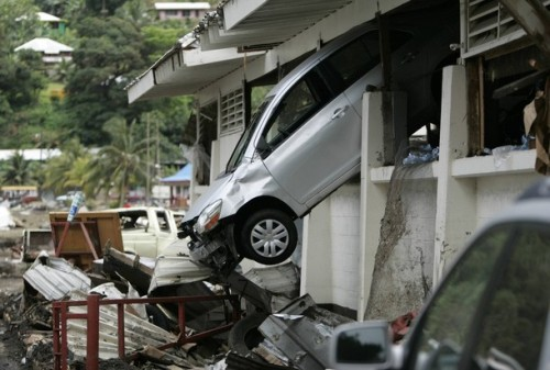 A car hangs from the wall of a building in Pago Pago Harbor after an earthquake caused a tsunami on the island of American Samoa, September 30, 2009. Relief workers in American Samoa and Samoa searched for survivors on Thursday after a series of tsunamis smashed into the tiny Pacific islands, killing more than 100 people, flattening villages and leaving thousands homeless.    REUTERS/Hugh Gentry (AMERICAN SAMOA DISASTER ENVIRONMENT)